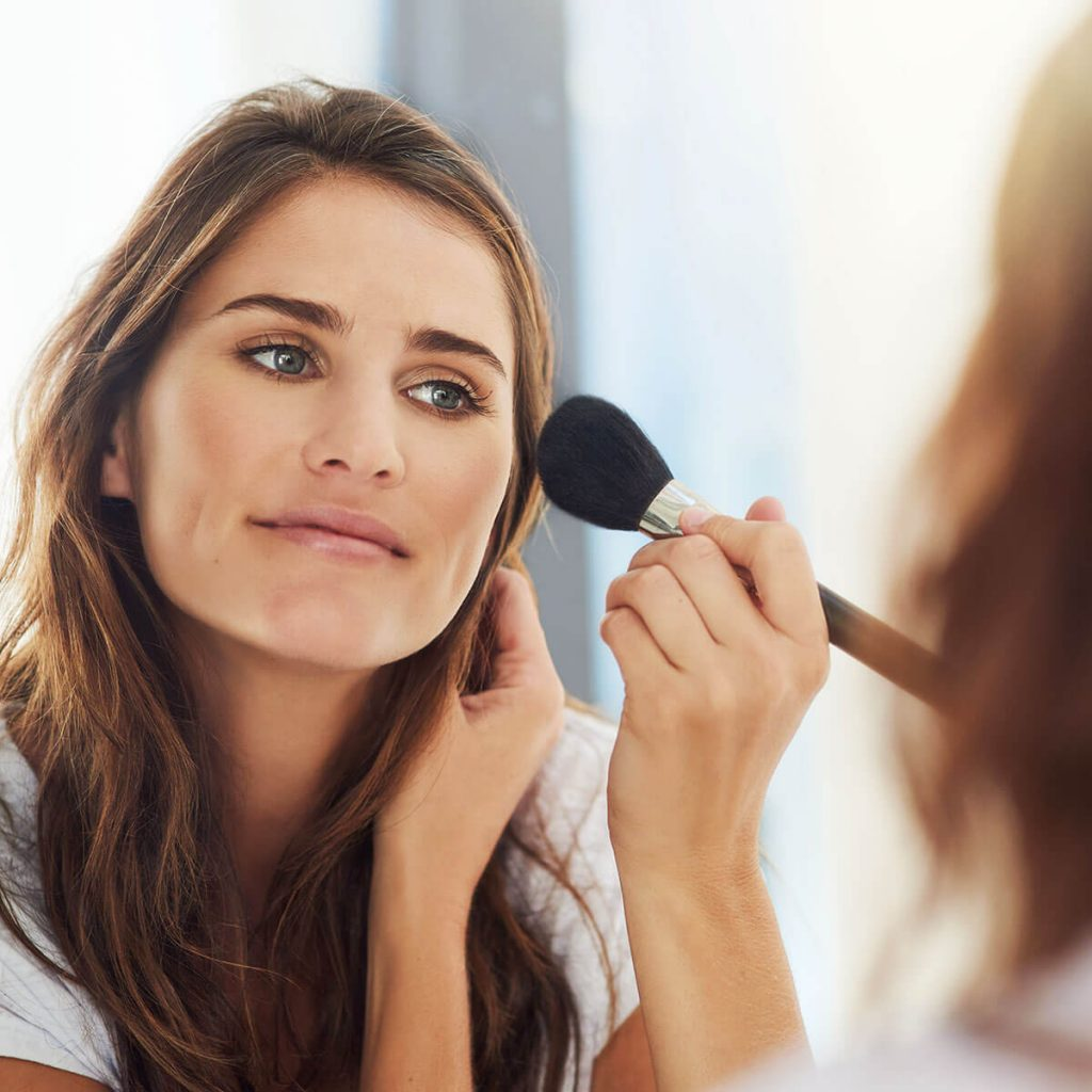 woman applying makeup blend for a natural look