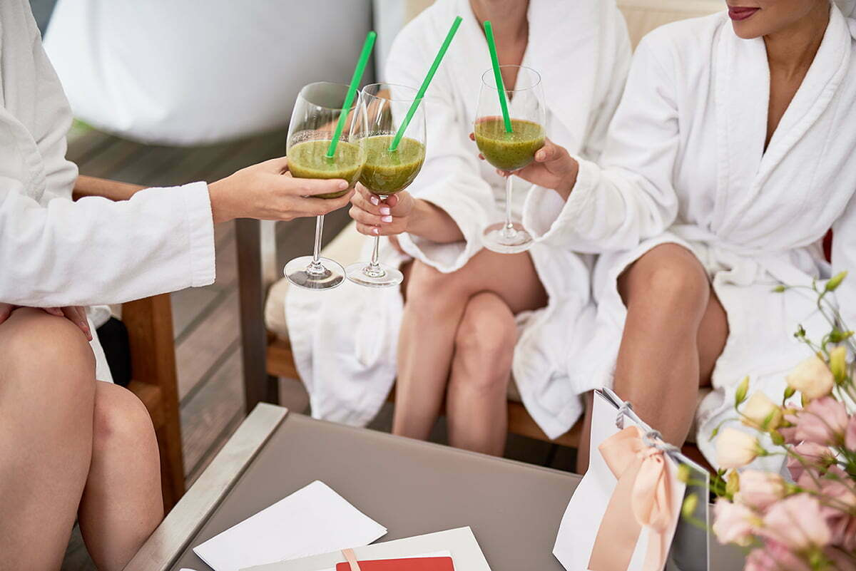 Three women drinking alcohol-free green juice
